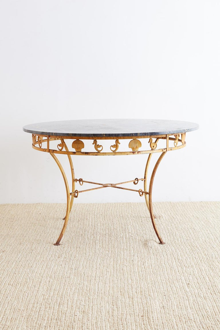 Captivating Mid-century marble garden patio dining table by Molla. Featuring a neoclassical style iron base decorated with their sea horses and shell motif design on the sides. Constructed from cast aluminium and supported by curved legs ending with