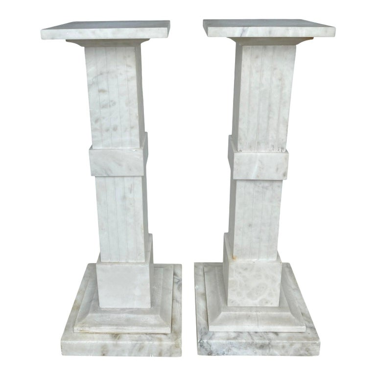 Impressive pair of neoclassical style white veined onyx stone pedestal columns. These large square columnar marble sculpture or plant stands feature square columns with fluted and band details atop stacked plinth bases. Each column is constructed of