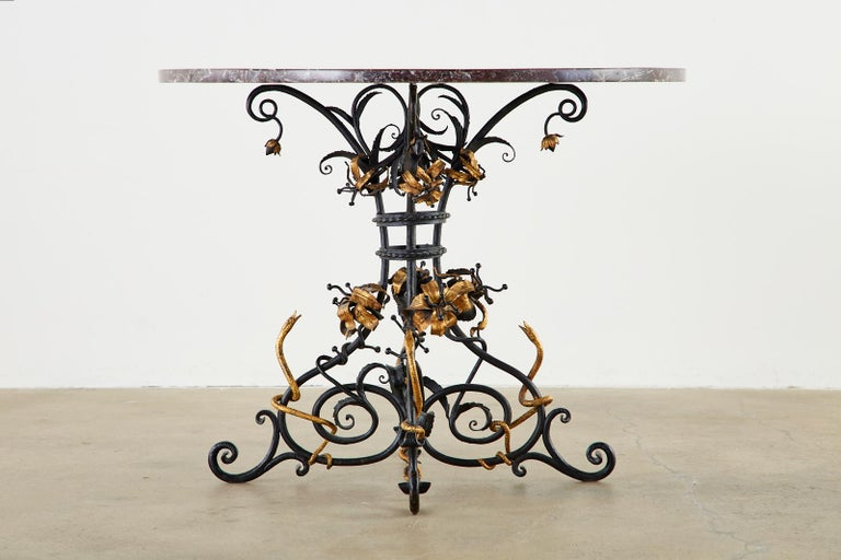 Dramatic Italian centre table featuring a Pietra Dura mosaic marble specimen round top. The 1 inch thick marble is inlaid with intricate neoclassical sunburst patterns centered with four snakes in an orb. Supported by an iron base with scroll legs