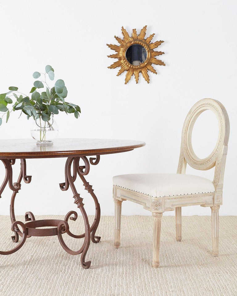Impressive Italian round dining table made of reclaimed oak and supported by a wrought iron base featuring decorative scrolled legs and feet. Solid oak top with lovely distressed wood look and a heavy iron base with a patinated iron finish.