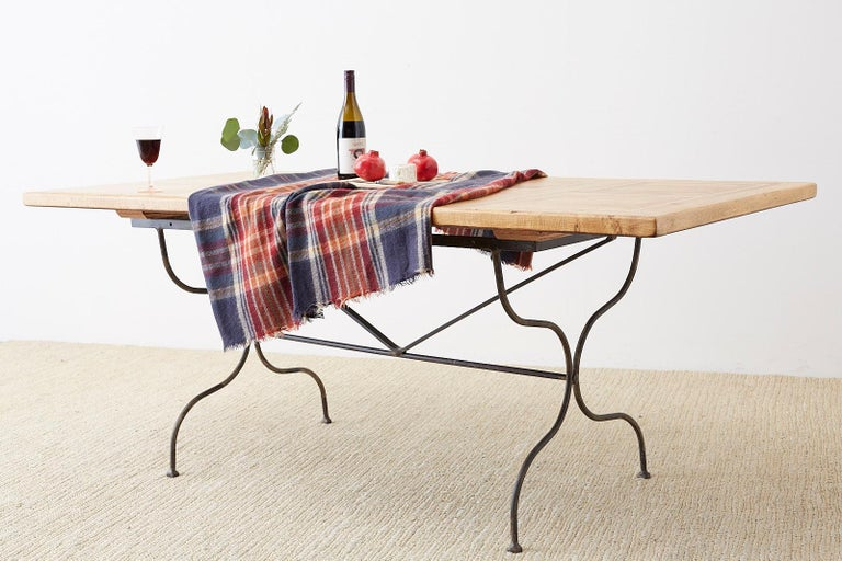 Rustic Italian farm table featuring an iron trestle style base. The thick oak top is constructed with geometrical inlay with square patterns on top. Excellent joinery and craftsmanship that showcases the rich oak grain patterns. The iron base has