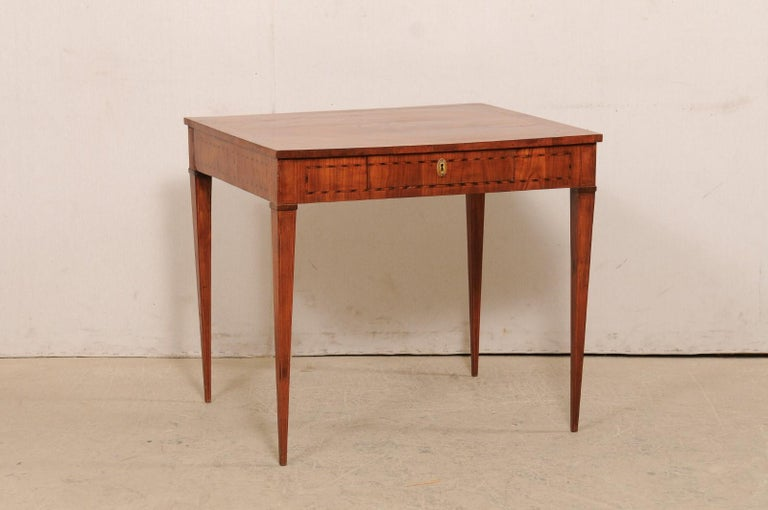 An Italian occasional table or small writing desk from the early 19th century. This antique table from Italy is beautifully decorated with a fanned medallion inlay featured prominently at it's top center, and a ribbon banding inlay outlines the top