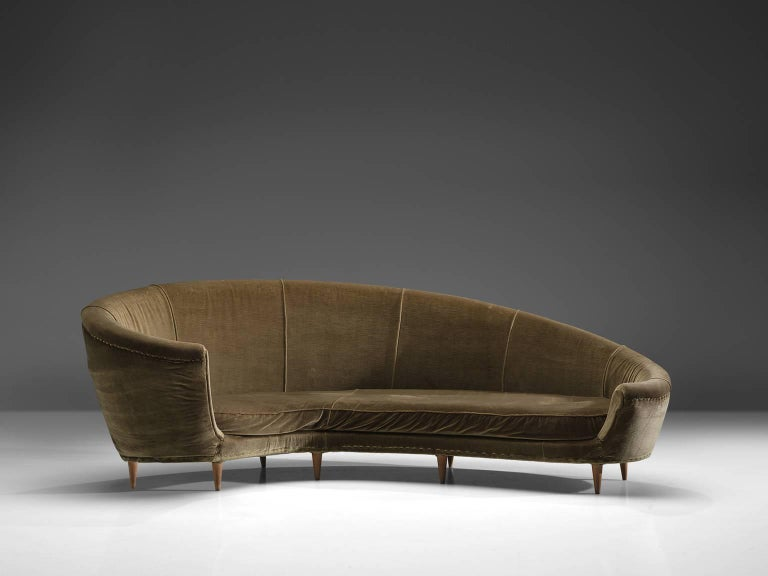 Settee, green velvet fabric, wood, Italy, 1950s  This dynamic sofa features an a-symmetrical back that is higher on the left side and slowly slopes towards much lower end on the right side. The six tapered delicate legs are executed in blond wood