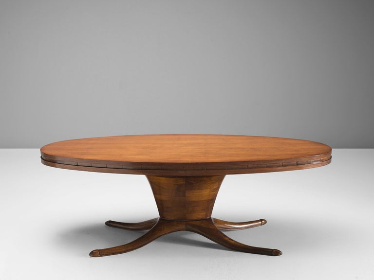 Dining table, walnut, Italy 1950s.  This oval dining table is made out of walnut veneer. The most striking detail of this table is the bas that is divided into a biomorphic shape. This element, combined with the oval base and oval top makes an