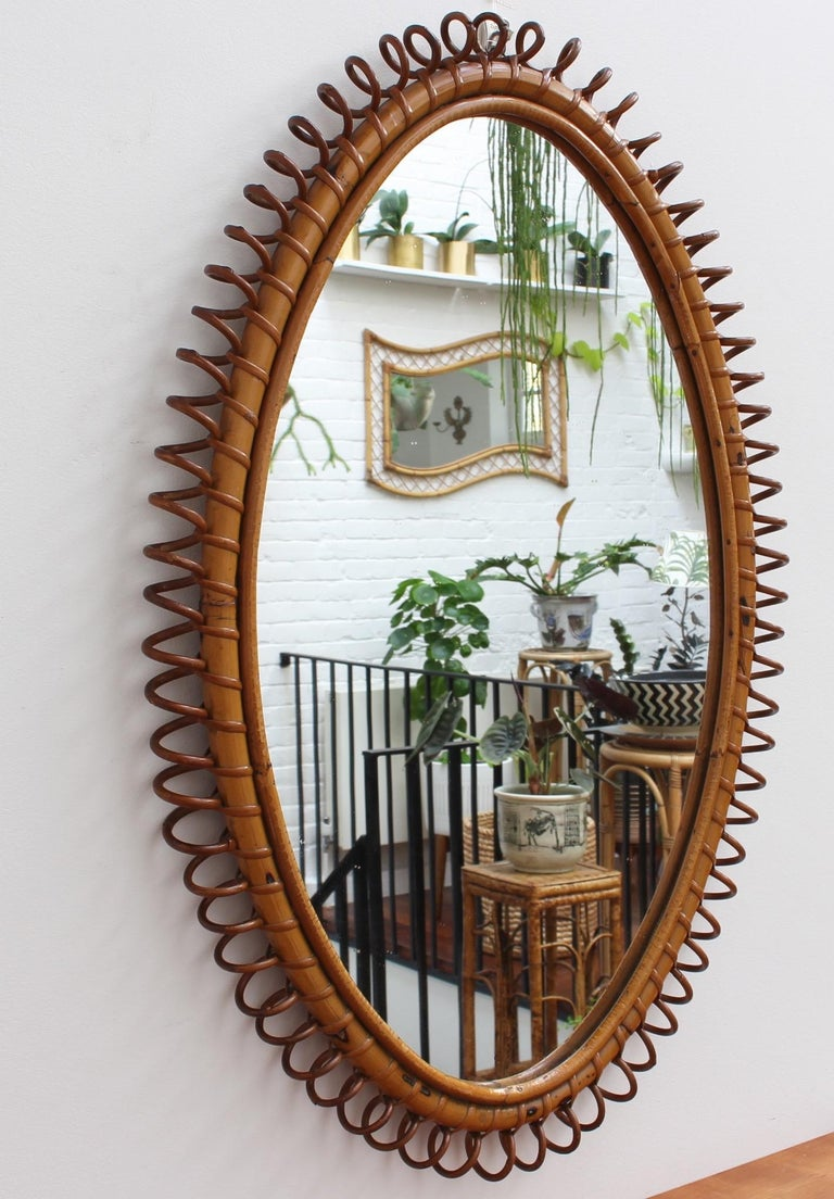 Italian rattan wall mirror (circa 1960s). This mirror has an oval form with delightful 'telephone line' shapes repeating around the rattan cane frame. The characterful, aged patina on the mirror frame attests to its age and adds to its charm. In
