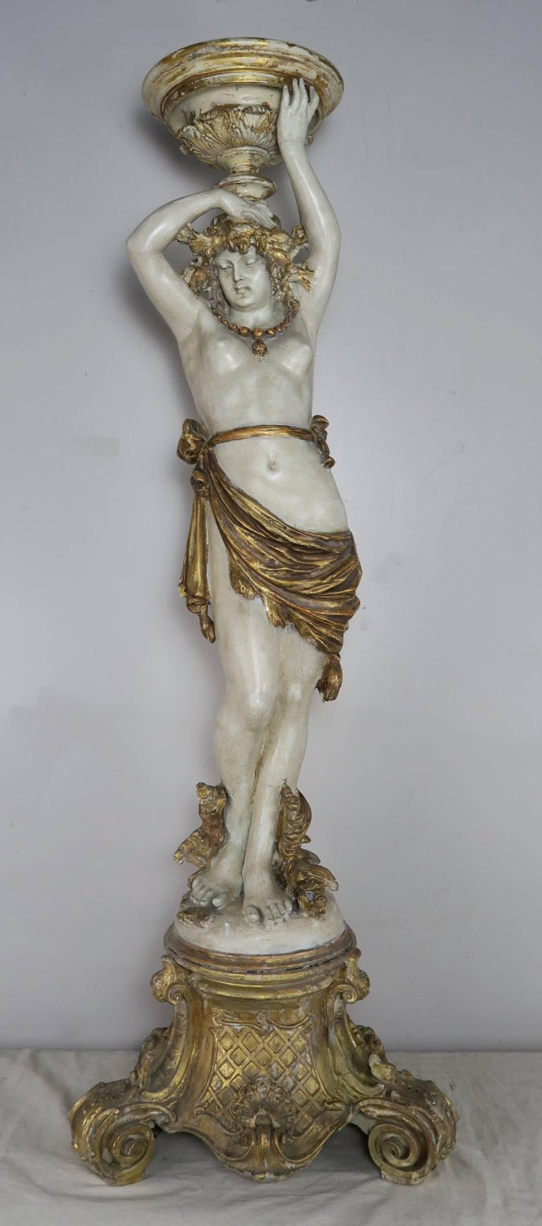 Italian Classical Roman style painted and parcel-gilt semi-nude torchiere standing on a beautifully carved giltwood base.