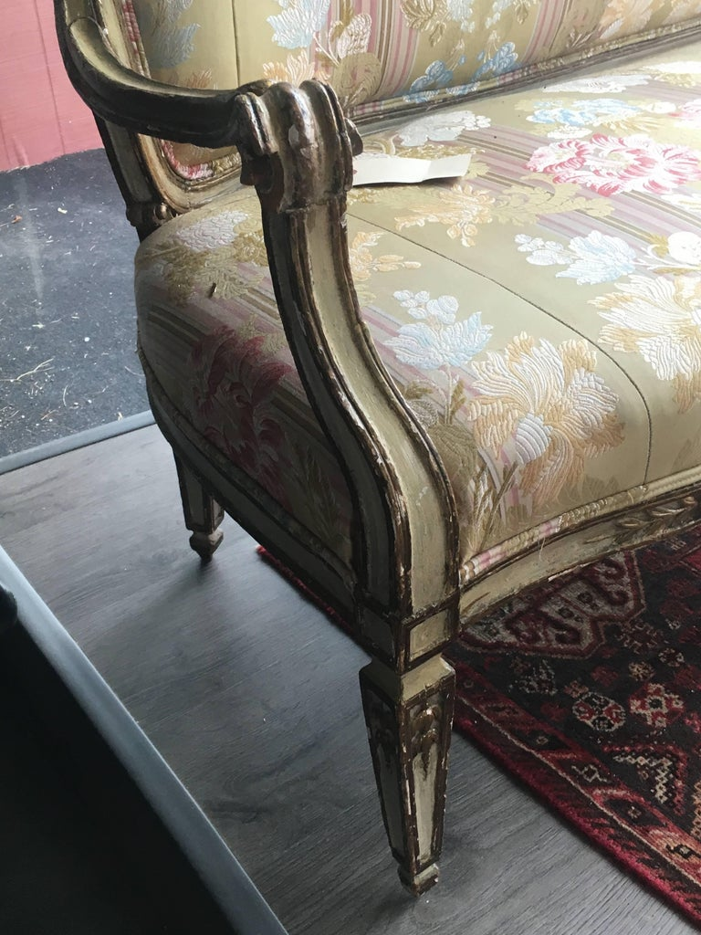 An Italian painted and parcel-gilt settee 18th century having a pierce carved ribbon crest over a padded back and a stuff over seat, raised on square tapering legs. Measure: Height 37 1/2 x width 69 x depth 23 inches.
