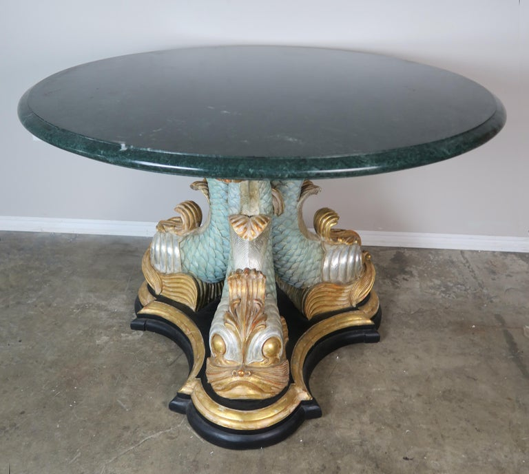 Italian soft aqua painted and parcel-gilt tripod dolphin carved wood table base. A green marble top with a single ogee and bullnose edge detail sits on the whimsical base.