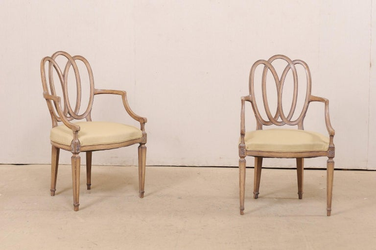 An Italian pair of carved wood armchairs with upholstered seats from the mid-20th century. This pair of occasional chairs from Italy have nicely entwined pierced oval-shaped backs, carved star accents adorn the apron at front seat rails, and they