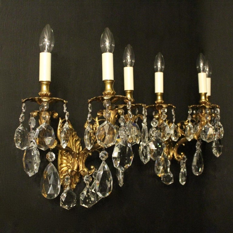 An Italian pair of gilded bronze and crystal triple arm antique wall lights, the leaf scrolling arms with leaf bobeche drip pans and bulbous leaf candle sconces, issuing from a foliated oval backplate and decorated overall with quality cut-glass