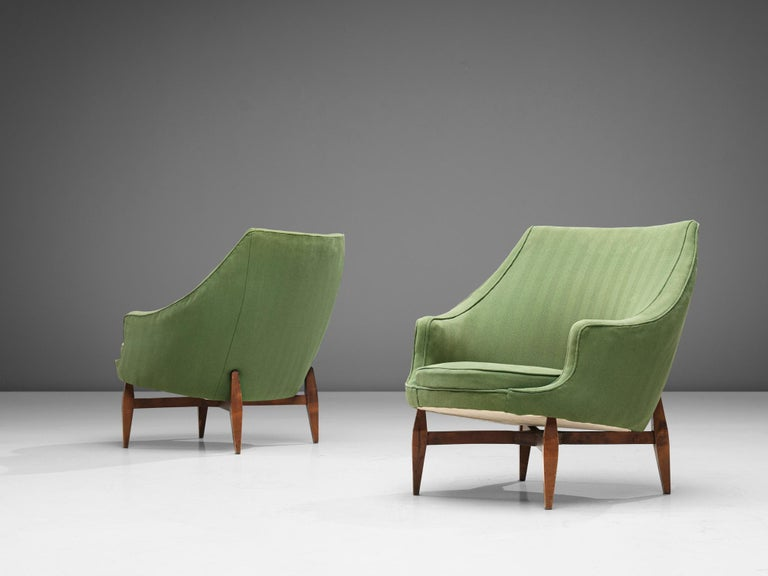 Pair of lounge chairs, fabric and beech, Italy, 1950s  A sensuous set of armchairs that features a sculptural back with short armrests and a round seat.The tapered wooden legs give the chairs a more airy touch and support the floating seating in an