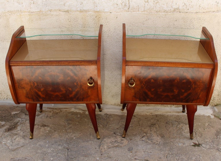 Rosewood pair of 1950s Italian nightstands or end tables. Brass bouts on the bottom of the feet. Attributed to Paolo Buffa. Rivers glass on top and glass shelf.