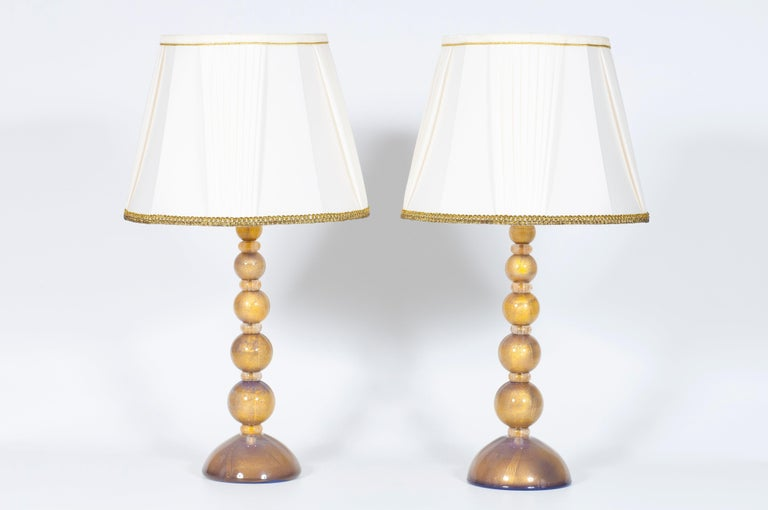 Italian pair of table lamps in Murano glass purple submersed in strong gold 21st century. This is an exclusive pair of table lamps, entirely manufactured in blown Murano glass. Each of them is made up of an entire body, having a shape of a series
