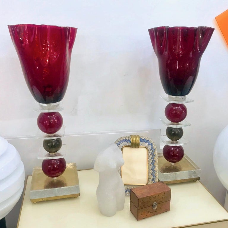 A charming pair of tall lamps in Murano glass, the blown red textured tops with a flowering shape are supported by a stem with three glass spheres in red and olive grey colors, on a clear glass square resting on a handcrafted bronze base raised on