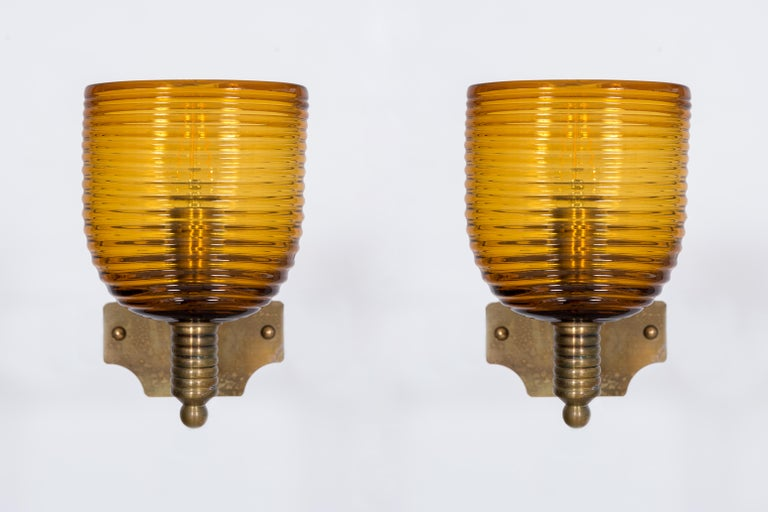 Italian Pairs of amber sconces in blown Murano glass antique brass frame, 1960s. Amazing and unique Italian Venetian, Pairs of Sconces, blown Murano glass, amber and brass 1960s, composed by an elegant amber bowl entirely handcrafted in blown