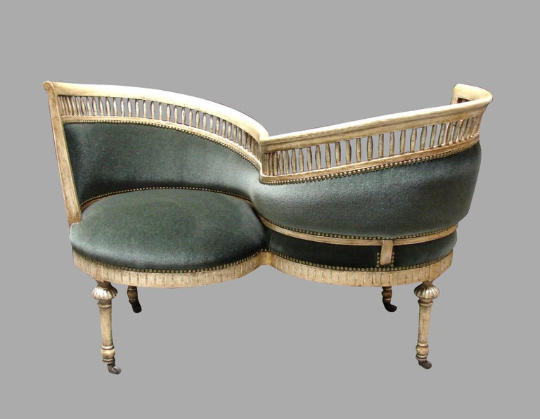 An elegant Italian parcel-gilt cream paint decorated serpentine form sociale or tete a tete, the spindle form top rail over a greyish green mohair upholstered back and seat, finished with nailhead trim over a carved seat rail supported on round