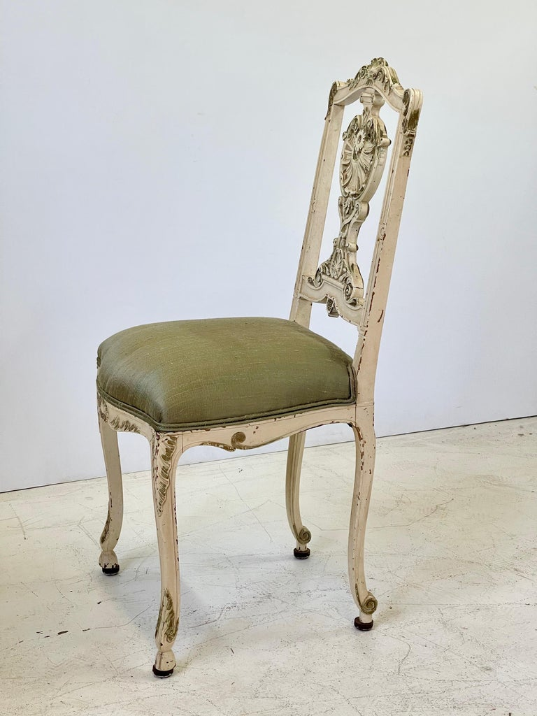 Early 20th century Italian vanity or petite side chair finely carved in the Louis XV style. The chair is painted in cream with gilded details that have beautifully worn over time. The seat has been newly upholstered in a complimentary green raw silk.