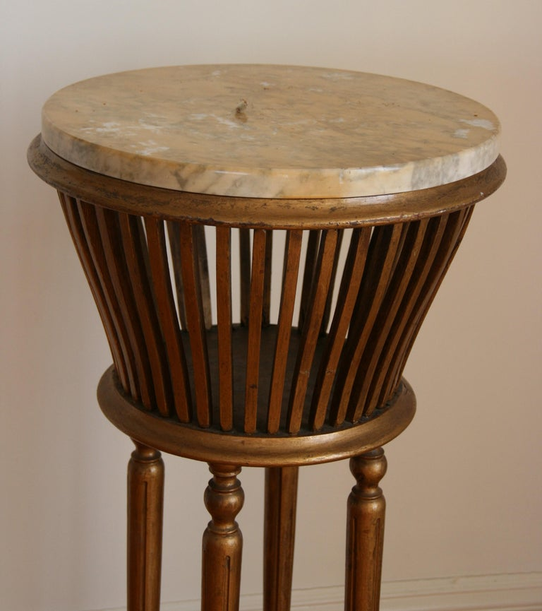 8-175 giltwood plant stand with marble top (someone added it) originally used to hold a plant. Can be use for either use Missing one wood stave.