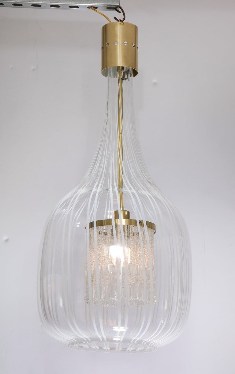 A unique and beautiful pendant chandelier by designer Angelo Brotto, (1914-2002) made for Esperia in blown Murano glass with white vertical lines, the interior fitted with a fringe which surrounds the light bulb creating a warm atmospheric glow. The