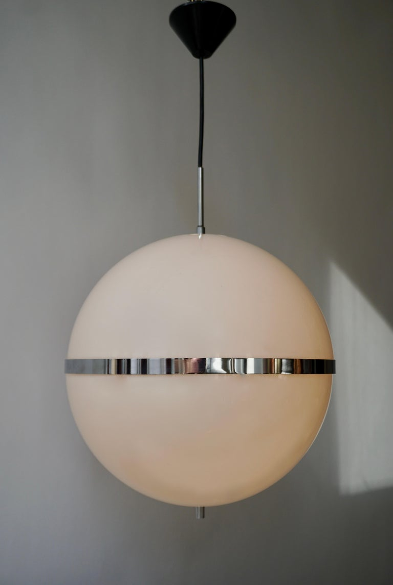 Rare and large pendant lamp in the style of Harvey Guzzini, Italy, 1960s-1970s. The light consists of a large sphere shaped shade in milky white plastic. These two parts are being complemented with beautiful chrome-plated metal details. This amazing