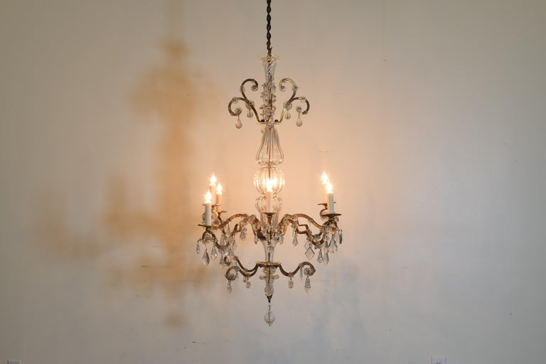 Having an iron frame with original gilding, the body of the chandelier is comprised of a number of blown glass sections, the arms mounted with glass rosettes and shaped glass prisms, center rod replaced to allow passage of wiring, UL wired.
