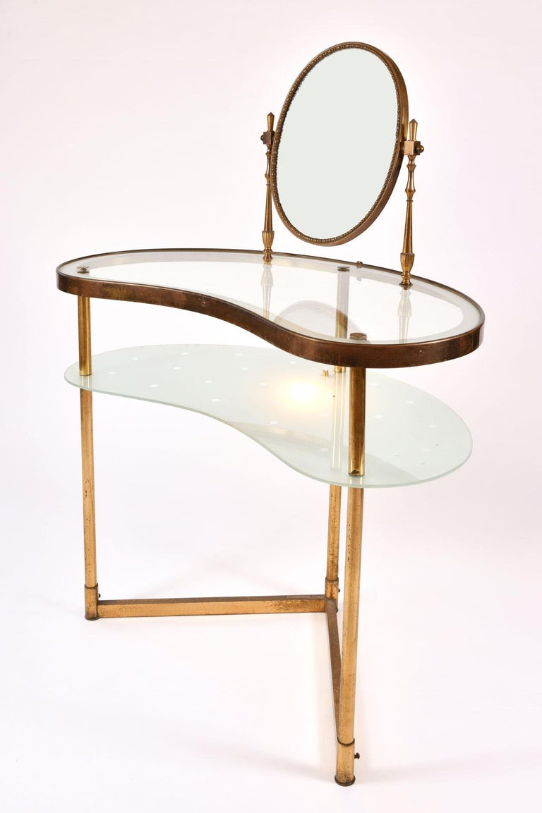 Two-tiered brass dressing-table with integral decorative oval mirror, the lower frosted glass shelf etched in polka dots with a fitted light for a touch of glamour, 1950s