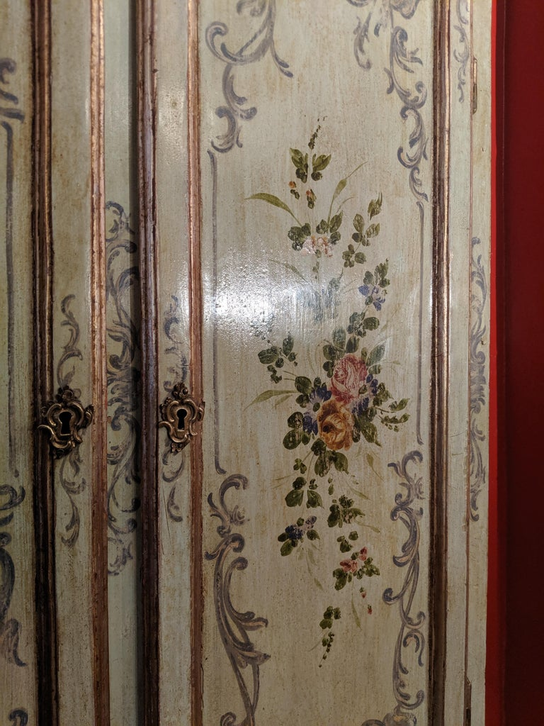 Italian polychrome Venetian bureau cabinet, first half of the 20th century. The Bureau painted throughout in a pale green with classical floral sprays in pinks and greens and a scrolling pale blue rococo style border, the rosette form handles in a