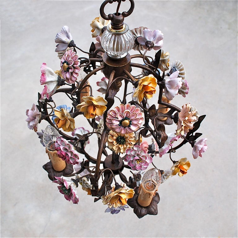 Floral pendant lamp or chandelier with a solid metal frame decorated with different style porcelain flowers in shades of pink, purple, yellow and white. The colourful, handmade flowers sit on metal stems with leaf detailing. Nestled among this