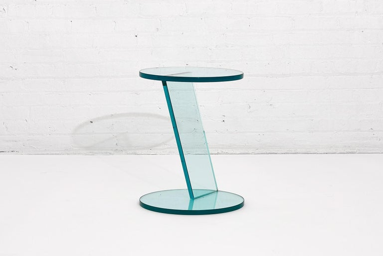 Italian Postmodern glass drink table. A Postmodern style round all glass table with asymmetric design, Italy, circa 1990s.