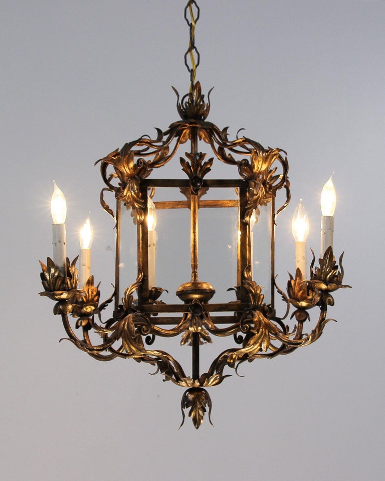 Beautiful, 1950s Italian gilt iron chandelier in the Provincial style. The chandelier features 6 arms flowing gracefully from a glass paneled lantern-shaped center. The chandelier's design and scale would make it a wonderful addition wherever it may