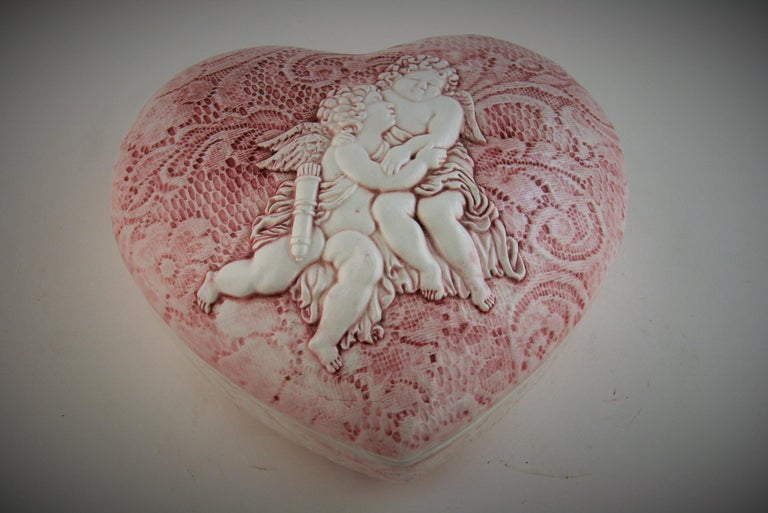8-239 Italian heart shaped ceramic box with embracing putti top. Rose colored embroidery detailing on top and bottom sections Marked made in Italy on bottom.