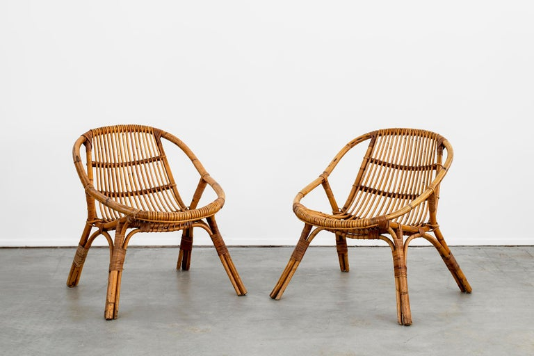 Sculptural pair of Italian rattan chairs with wonderful scoop shape.