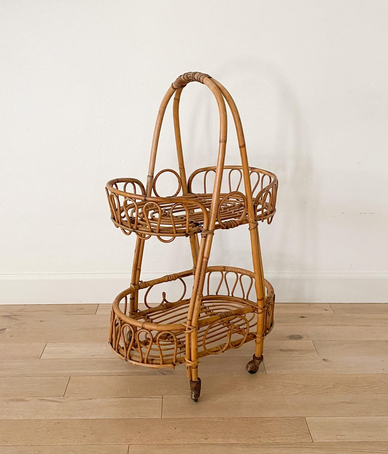 Italian 1960s rattan and bamboo bar cart from Italy. Oval cart with two tiers, handle, and 4 original metal casters. Beautiful original condition and new wood and brass casters.