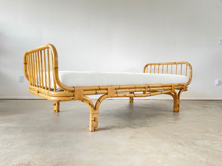 Italian bamboo daybed. Reupholstered in crisp white linen.  Sculptural bamboo headrest and footrest.