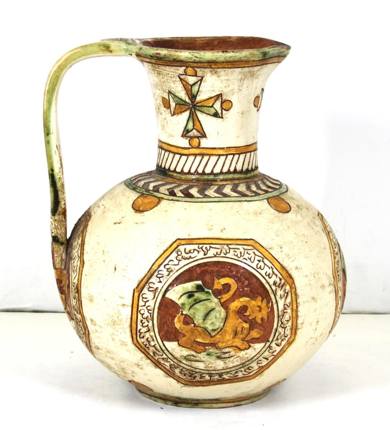 Italian Renaissance Revival ceramic pitcher with sgraffito decor of Maltese crosses on the neck and medallions depicting dragons. Made in Italy during the 1900s, this piece is in remarkable antique condition with age-appropriate wear and use.