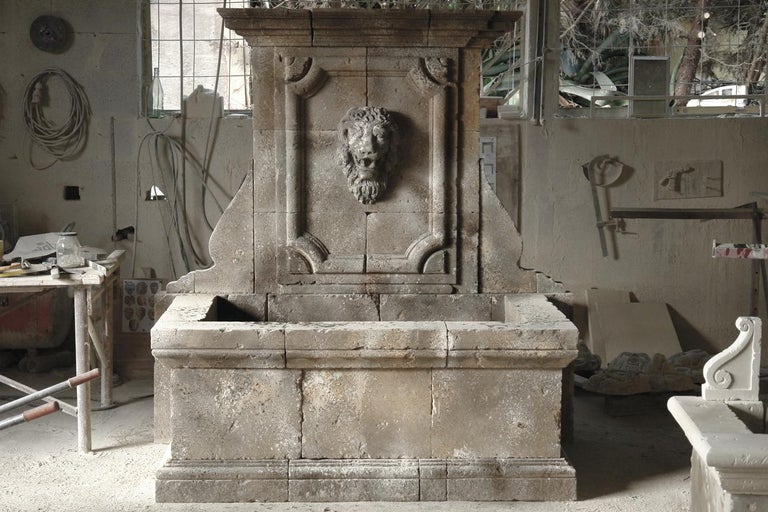 An Italian Renaissance style wall fountain, hand-carved in pure limestone with antique patina. Exceptional art work with tradition, with deep carving on panel and basin, as well as for the heads lions hand carved as well with details. Ready for