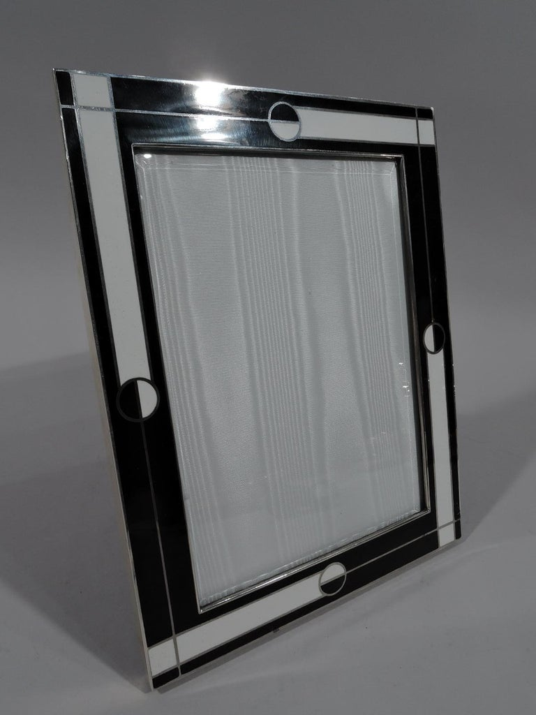 Italian Retro Deco sterling silver and enamel frame. Rectangular window and flat surround with contrasting black and white geometric ornament inset with silver grid. Sides silver. Bold 1980s-era design for a power-suit portrait. Shoulder pads not