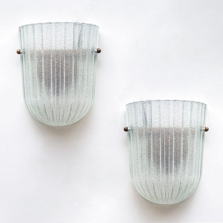 Beautiful pair of Italian ribbed glass sconces with brass ball detailing. Oblong frosted glass with wide ribbed detail on glass. New brass interior fitting and socket.