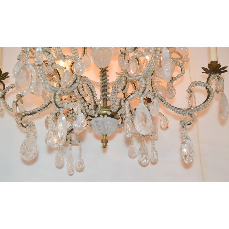 Fabulous French rock crystal chandelier. The stem and branches abundantly wrapped in crystal beads. Exquisitely decorated overall with carved rock crystal medallions, fruits, and prisms, and having leaf spray motif bobeche. The base with a rock