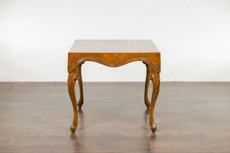 An Italian Rococo style walnut and olive wood square top side table from the mid-20th century, with cabriole legs. Created in Italy during the midcentury period, this walnut and olive wood side table charms us with its square top adorned with a