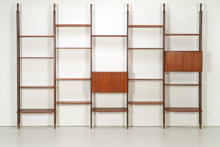 Large mid-century bookcase by Paolo Tilche from the 1960s. The shelf is made of teak and is particularly characterized by a maximum height of 320 cm, the minimum height would be 275 cm. Black steel clamps are screwed to the floor and ceiling, into