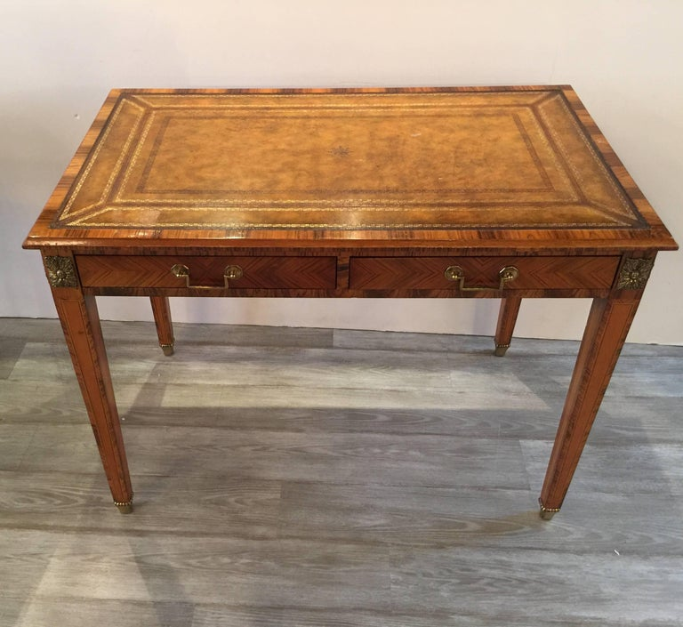 Handsome rosewood and leather desk with ormolu mounts. The warm leather top with figurative rosewood frame and legs. The apron with two drawers. The tapering legs with rosewood along the sides. The top has to pull out trays that extend the sides 11