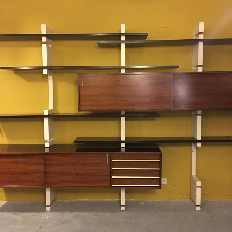 Italian rosewood and white wooden Extenso bookcase by AMMA Torino, 1960s Extensible rosewood wall Extenso bookcase with white enamelled wooden uprights and brass details Composed of two container modules, one with sliding doors and the other with
