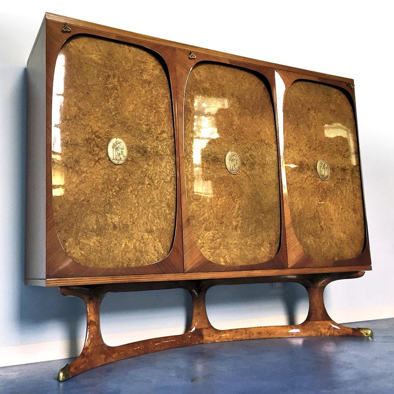 Rare sideboard three-doors designed by Vittorio Dassi in the 1950s. It's a very fine item made using precious materials, the structure of the cabinet is rosewood and the three-doors are in birch briar root, finished with brass medallions positioned