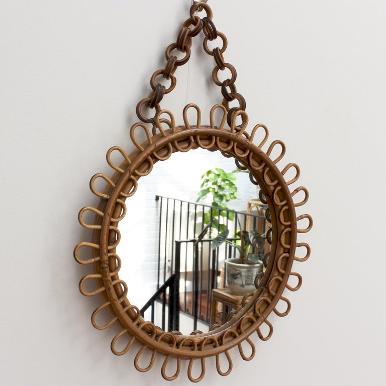 Italian round rattan wall mirror with chain (circa 1960s). This mirror has a very charming round shape with rattan spirals framing the mirror. The rattan hanging chain adds further allure. There is a characterful, aged patina on the mirror frame. In