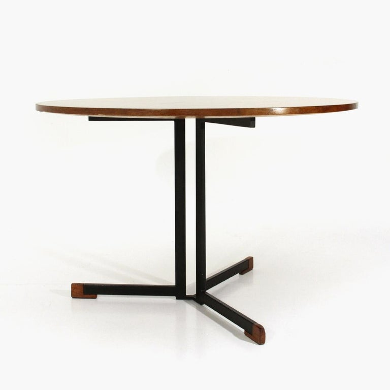 Italian-made table produced in the 1950s. Central leg in black painted metal with wooden terminals. Round top in veneered wood with tapered lower edges. Fair general conditions, signs and lacks of veneer due to normal use over