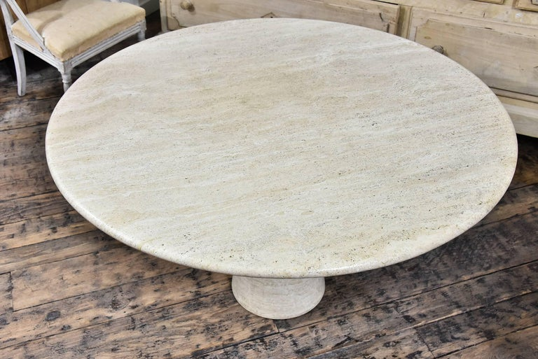Sophisticated travertine pedestal table in warm cream and beige tones, excellent condition.