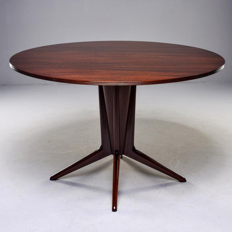 "Italian walnut table with versatile 48"" round top, circa 1960s. Sculptural four-footed pedestal base. Unknown maker."