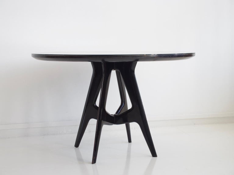 Round table made of lacquered wood and with tabletop cover of glass. Produced in Italy, circa 1950s. In great vintage condition.