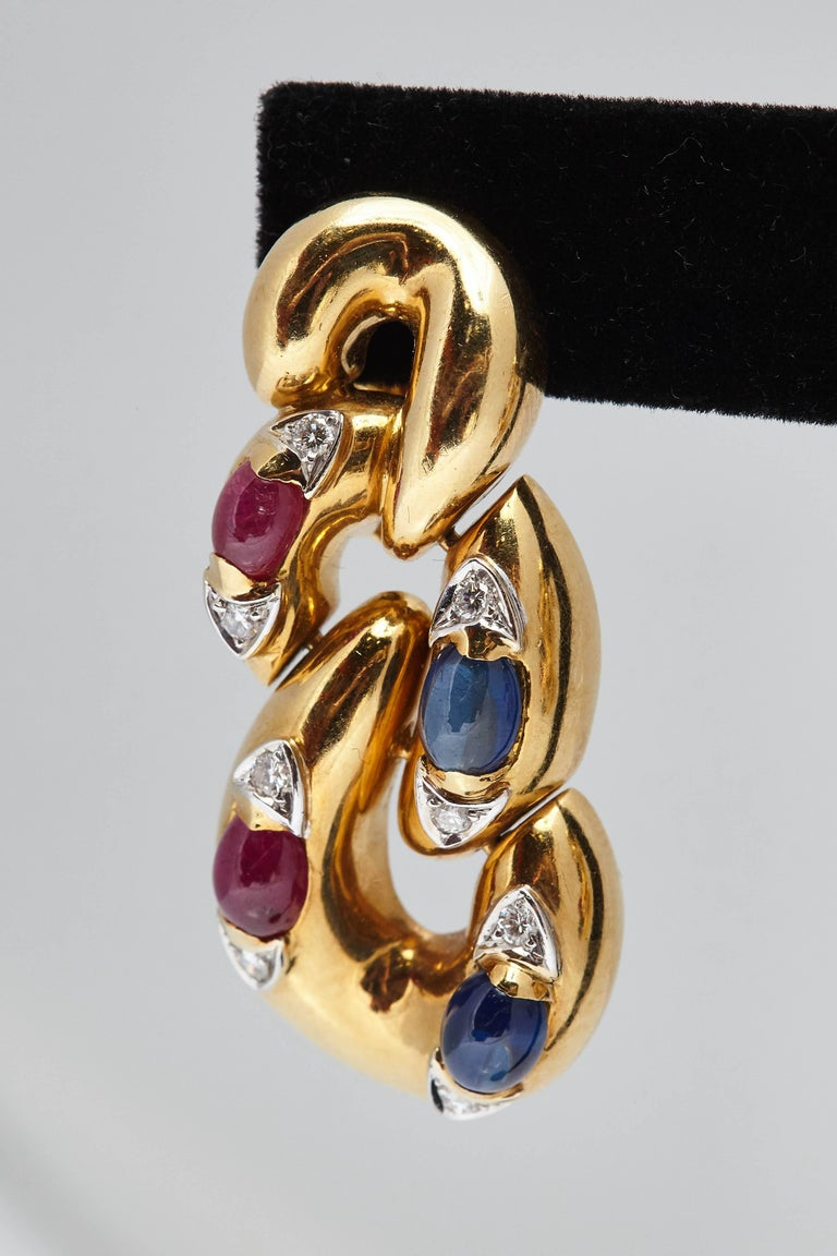 A pair of peculiar 18kt yellow gold ear pendants with cabochon sapphires, cabochon rubies and diamonds. Made in Italy, circa 1970s